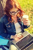 education, technology and internet concept - smiling redhead teenager in eyeglasses with laptop computer and take away coffee or tea