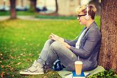 summer holidays, internet and technology concept - teenager with headphones, books, coffee and tablet pc outside