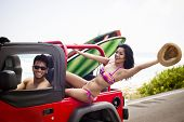 Young adventurous couple ready to surf at the beach with a red car