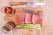 meat food : raw beef fillet on cutting board with asparagus and thyme bundle , with color peppercorn