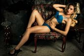 stock photo of bombshell  - A young slim attractive blond woman wearing sexy blue bra an panties reclining provocatively on chair - JPG
