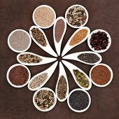 Large seed super food selection in porcelain bowls over brown lokta paper background.