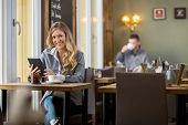Portrait of young pregnant woman using digital tablet at table in coffeeshop