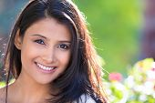 stock photo of indian  - Closeup headshot portrait of confident smiling happy pretty young woman isolated background of blurred trees flowers - JPG