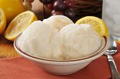 stock photo of gelato  - A bowl of lemon sherbet or gelato near a basket of grapes - JPG