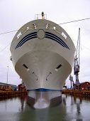 stock photo of shipbuilding  - A large white and blue tanker ship being renovated in a shipyard - JPG