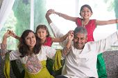 Happy Indian family at home. Asian parents playing with their kids, sitting on sofa. Parents and chi