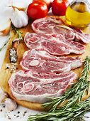 Raw Lamb Cutlets With Vegetables, Herbs And Spices On Wooden Chopping Board