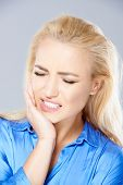 Beautiful young blond woman wincing in pain holding her hand to her jaw and closing her eyes against