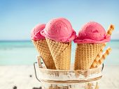 Fresh fruit ice cream scoops in cones, blur beach on background