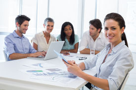 stock photo of half-dressed  - Attractive businesswoman smiling at the camera during a business meeting while using a tablet - JPG