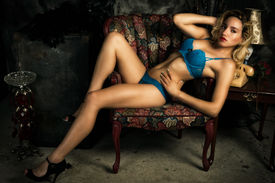 stock photo of panties  - A young slim attractive blond woman wearing sexy blue bra an panties reclining provocatively on chair - JPG