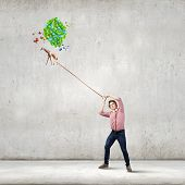 Young guy in casual and giraffe flying away on balloons