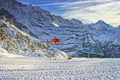 Red Helicopter Flying Near Swiss Ski Resort Near Jungfrau Mountain