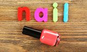 Nail word formed with colorful letters on wooden background