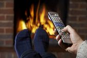 Man With Remote Control Watching Television And Relaxing By Fire
