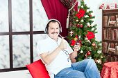 Man Listening To Music On Headphones  Near A Christmas Tree