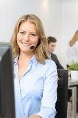 Attractive smiling woman at her desk with handset with people working at the background