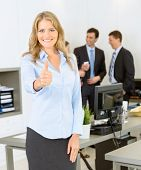 Portrait of an attractive businesswoman with thumbs up and her colleagues in the background