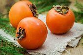 Three Fresh Organic Persimmon On Wooden Background