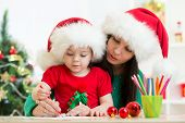 Child girl and mother writing christmas letter to Santa