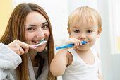 mom and child son brushing teeth in bathroom