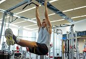 sport, fitness, lifestyle and people concept - young man flexing abdominal muscles on pull-up bar in gym