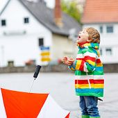 Happy Smiling Little Boy Walking In City And Playing With Red Umbrella