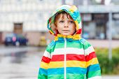 image of rainy season  - Happy smiling kid boy walking in city through rain wearing colorful rain coat and green boots outdoors at rainy day - JPG