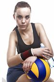 Tanned And Exhausted Caucasian Female Volleyball Athlete Sitting With Water Bottle And  Ball. Agains