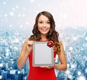 christmas, holidays, technology and people concept - smiling woman in red dress with tablet pc computer over snowy city background