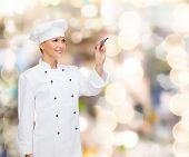 cooking, holidays, advertisement and people concept - smiling female chef, cook or baker with marker writing something on virtual screen over lights background