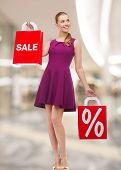 people, gifts, christmas and holidays concept - smiling young woman in dress holding shopping bags with percent and sale sign over mall background