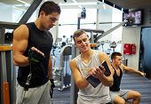 sport, fitness, lifestyle and people concept - men with clipboard taking notes and exercising on gym machine