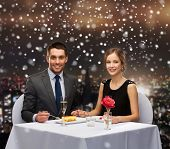 food, christmas, holidays and people concept - smiling couple eating dessert at restaurant over snowy night city background