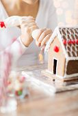 cooking, people, christmas and decoration concept - close up of woman making gingerbread houses at home