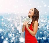 christmas, holidays, sale, banking and people concept - smiling woman in red dress with us dollar money over snowy city background