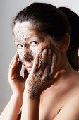 Mature woman making cosmetic mask .