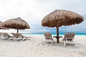 Sun Umbrellas And Chairs On Caribbean Beach