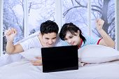 Couple With Laptop On Bed In Winter Day
