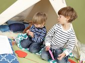 stock photo of teepee  - Kids engaged in arts and crafts activity playing in a teepee tent at home - JPG