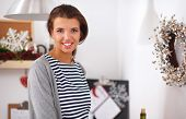 Smiling young woman in the kitchen, isolated on christmas background