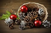 Christmas Concept (decoration). Basket With Red Ball And Cone  On Rustic Wooden Background