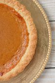High angle closeup of an fresh baked pumpkin pie on a holiday plate. The dessert is on a gold charger on a white wood table. Vertical format.
