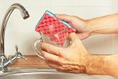Hands with sponge and dirty cup over the sink in kitchen