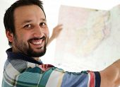 Adult man with bear holding big paper map and looking for right way