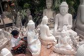 Polishing A Marble Buddha Statue.