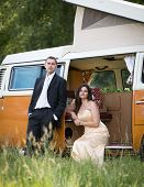 pic of campervan  - Happy just married couple in an orange classic camper van parked outside in a green field ready for camping and a piknick - JPG