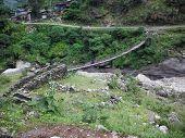Suspension Bridge Over River In Rural Himalayas