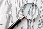 Single Magnifying Glass On Top Of Business Reports